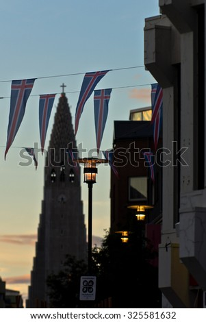 Islandic flags in front of Hallgrimskirkja church, Reykjavik cathedral with modern scandinavian architecture at sunrise, Iceland - stock photo