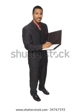 Isloated full length studio shot of an African American businessman writing on a notepad.