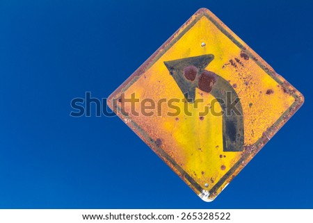 Isolate sign, turn left Old weathered and rusted with blue sky in the background. - stock photo