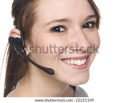 Isolate studio shot of a casually dressed young adult woman smiling while talking on her telephone headset.