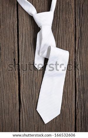isolate white necktie on wooden table - stock photo