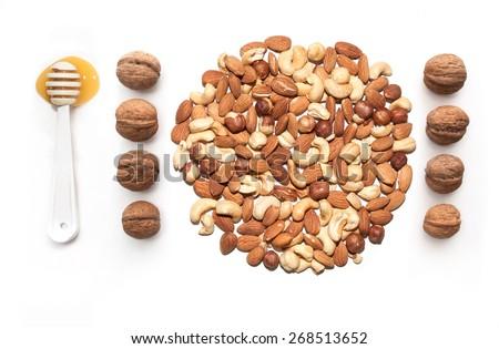 isolated almonds, cashew, hazelnut walnut and spoon with honey - stock photo