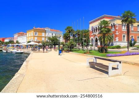 Isolated bench near the Adriatic sea shore, town and harbor of Porec, Croatia - stock photo