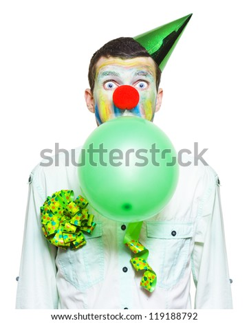 Isolated Birthday Clown In Party Costume, Looking Surprised.While Blowing Up Green Balloon Over White Background - stock photo