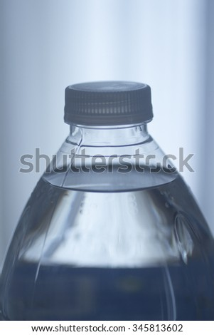 Isolated blue plastic water bottle on a plain blue studio background close-up photo. - stock photo