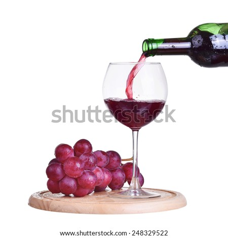 Isolated bottle with red wine, glass and grape on wooden plate - stock photo
