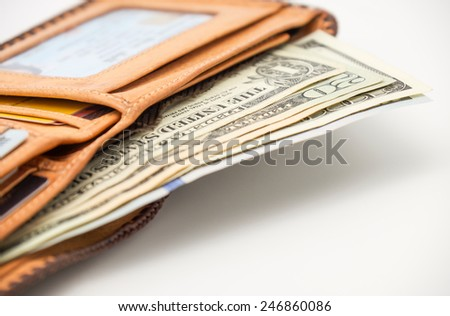 Isolated brown leather wallet / purse with us money banknotes on white background  - stock photo