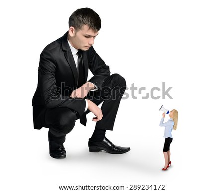 Isolated business man looking at little woman - stock photo
