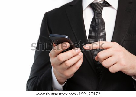 Isolated businessman in a suit and tie holding a touch phone - stock photo