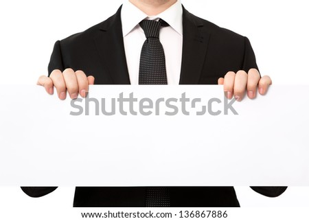 Isolated businessman in a suit holding a large white sheet of paper or banner - stock photo