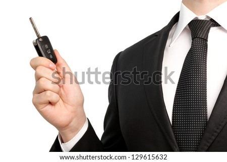 Isolated businessman in suit and tie holding a car key - stock photo