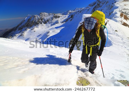Isolated climber traveling on snow covered mountain in sunny winter day