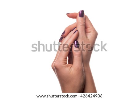 Isolated close up on female hands in relaxed gesture with purple fingernail polish over white background - stock photo