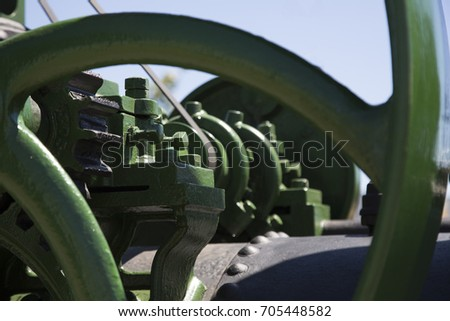 Isolated Close View of Green and Black Painted Antique Mechanical Gears and Steam Engine, Blue Sky in Background