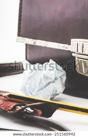 Isolated crumpled paper with leather bag in white background.