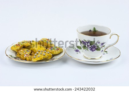 Isolated cup of english tea whit sweet and decored cookies - stock photo