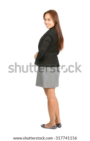 Isolated cut out of rear view of Asian businesswoman boss in black jacket, casual gray dress with beautiful smile looking back over her shoulder at camera. Thai national of Chinese origin. Full length