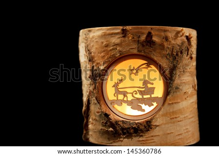 Isolated decorative Christmas tea light depicting Santa on a reindeer sleigh - stock photo