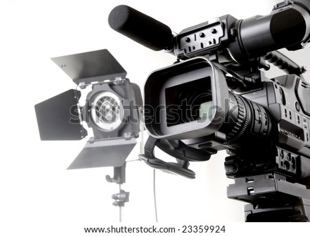 isolated digital video camera recorder on tripod  and spot light with white background - stock photo