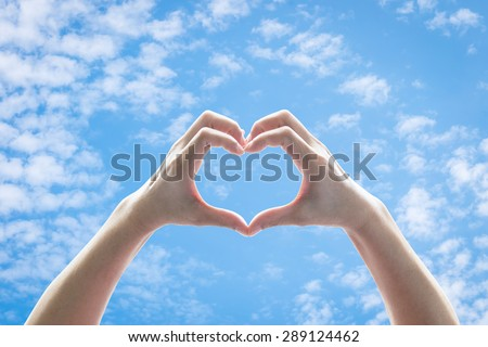 Isolated female human hands in heart shape raising against blue sky with clouds background: Universal hand sign language meaning love and caring: Preservation of ozone layer and climate concept
