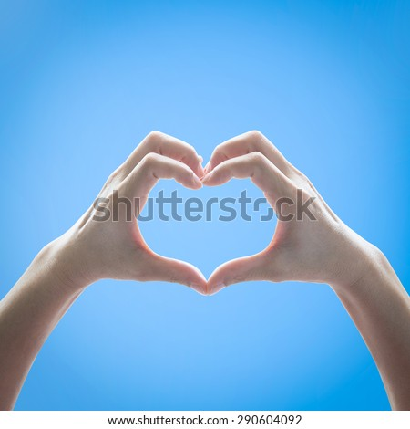 Isolated female human hands in heart shape raising against clear bright blue sky background: Universal hand sign language expression meaning love, caring, friendship