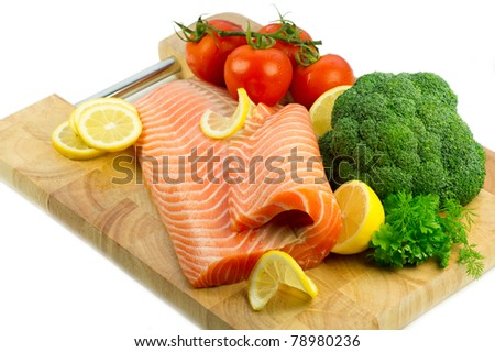 Isolated fresh raw red fish with lemon, broccoli, greenery and tomatoes on the wooden cutting board - stock photo
