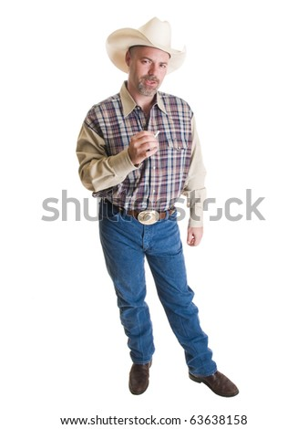 Isolated full length stock photo of a cowboy preparing to smoke a cigarette. - stock photo