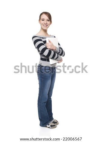 Isolated full length studio shot of a casually dressed young adult female college student holding a laptop computer. - stock photo