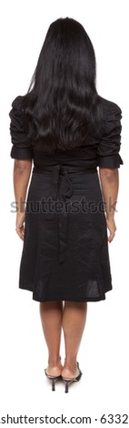 Isolated full length studio shot of a Latina businesswoman facing away from the camera with arms at her sides. - stock photo