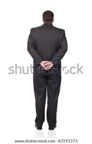 Isolated full length studio shot of the back side of a businessman facing away from the camera with his hands clasped behind himself. - stock photo
