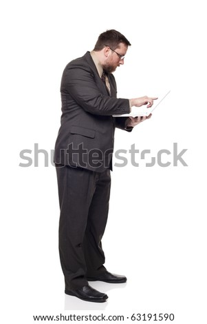 Isolated full length studio shot of the side view of a businessman working on a laptop he is holding while standing - stock photo