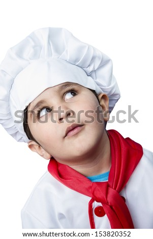 Isolated funny boy dressed in chef, cooking in a kitchen - stock photo