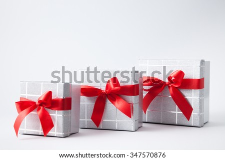 Isolated gift boxes with red satin ribbons on white background