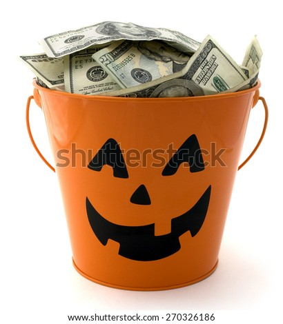Isolated halloween bucket filled with cash. - stock photo