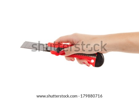 Isolated hand of a woman holding a cutter against a white background.