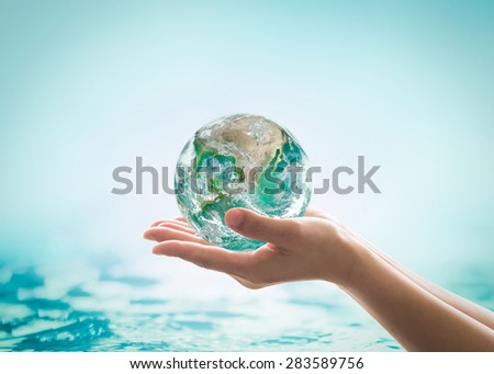 Isolated hands holding green planet on turquoise green water background : World ocean day and hydrography concept: Elements of this image furnished by NASA  - stock photo