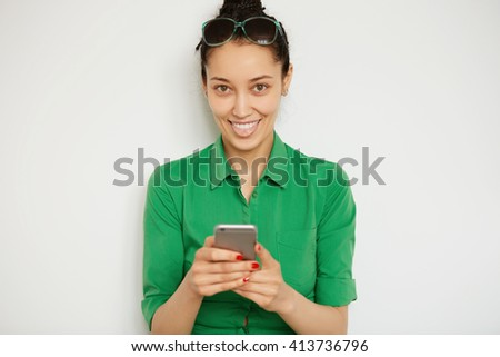 Isolated headshot of funny brunette girl showing tongue holding cell phone and posing against blank copy space wall. Young woman having fun while chatting with friend on mobile phone. Selective focus - stock photo
