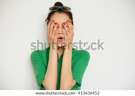 Isolated headshot of funny girl in casual shirt covering her face with both hands. Young female model having fun while posing on white copy space background. Human face expression, body language   - stock photo