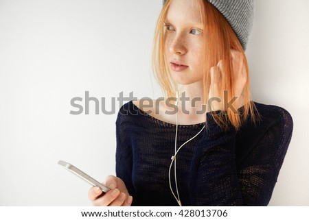 Isolated headshot of pretty redhead student girl with freckles in gray cap wearing earphones, looking away with attentive expression while listening to audiobook, preparing for exams at university.  - stock photo