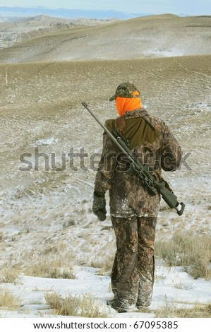 Isolated image of hunter with rifle.  Image taken during big game hunting trip in Wyoming. - stock photo