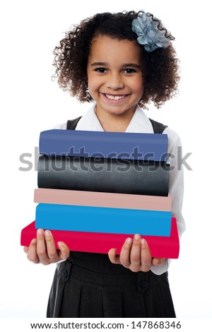 Isolated little girl carrying pile of books - stock photo