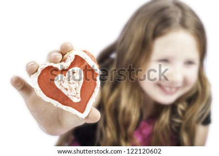 Isolated little girl holding a heart cookie for valentines day with her blurred in the back - stock photo