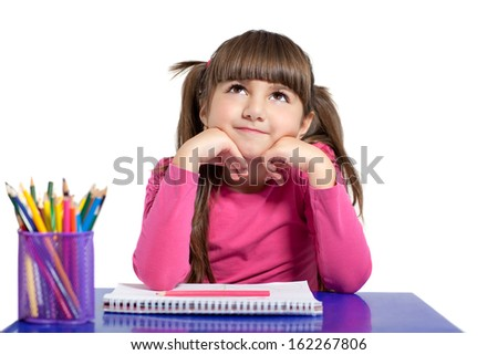 isolated little girl in a pink shirt is sitting at the table with colored pencils  - stock photo