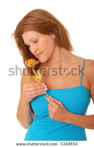 Isolated lovely and sexy young brunette girl holding a golden rose