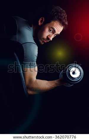 Isolated male working out with weights. Low-key lighting with black background and spotlights.