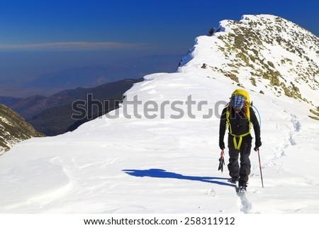 Isolated mountaineer walking along snow covered mountain ridge - stock photo