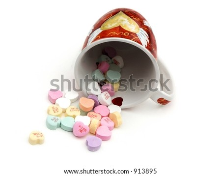 isolated mug spilled over with candies - stock photo