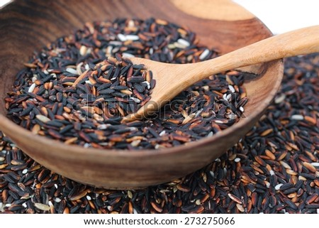 isolated of black rice in wooden blow - stock photo