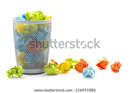 isolated office wastepaper basket with colourful crumbled paper ball - stock photo