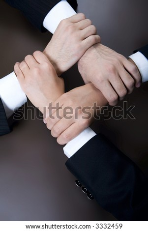 Isolated on black four crossed human hands in business wear